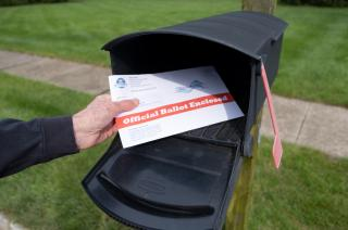 Man depositing an official ballot into a mailbox