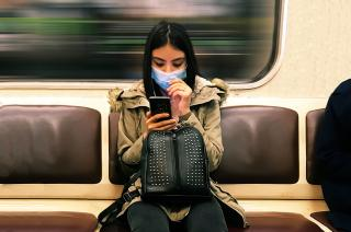 Young woman wearing a medical mask in subway train while texting on mobile phone