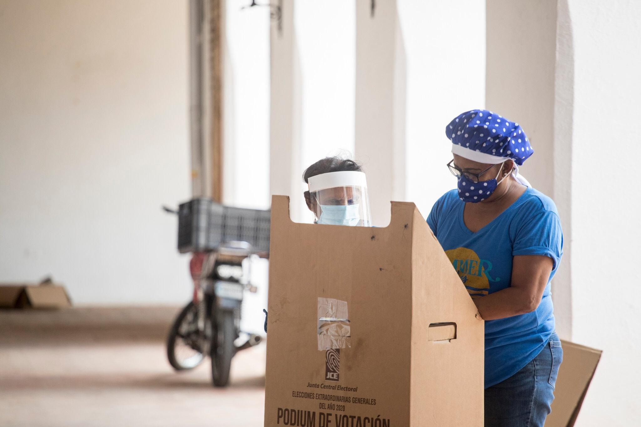 Una mujer ayuda a su madre a votar en Santo Domingo durante las elecciones presidenciales de República Dominicana