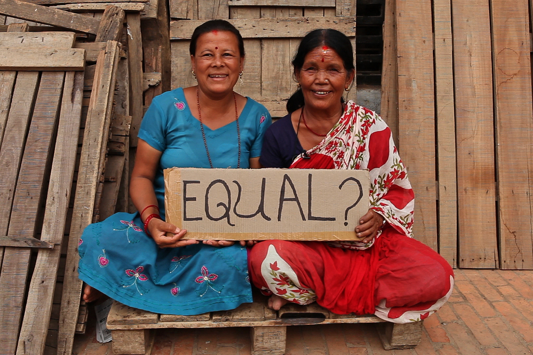 """Two women in Nepal hold a sign reading, """"Equal?""""  Video still by Stephan Bachenheimer/World Bank."""