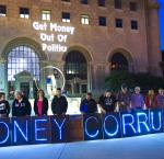 People holding a sign that read, 'Money Corrupts' outside of Milwaukee County Court. 'Get money out of politics' is projected on the wall behind them.