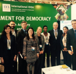 Opening ceremony of the International IDEA stand, group picture with International IDEA staff, H.E. Mr. Gonzalo Gutiérrez, Ambassador of Peru in Brussels, Mr. Hamed Zekri, Councellor at the Embassy of Tunisia in Brussels, and stand visitors.