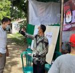 A voter's body temperature being checked as a safety measure at a polling station in South Tangerang City, Banten Province. Image credit: Hadar Gumay/Netgrit.